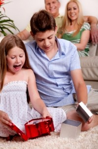 Kids Opening Christmas Gifts With Parents In The Background Stock Photo by photostock